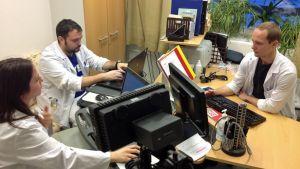 Lääkäreitä tutkimassa potilasasiakirjoja tietokoneelta.