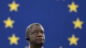 Denis Mukwege kuuntelee EU:n istuntoa luuri korvallaan. Taustalla EU:n sinikeltainen lippu.