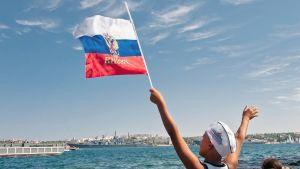 Poika heilutti Venäjän lippua katsoessaan Venäjän laivaston paraatia Sevastopolin edustalla.