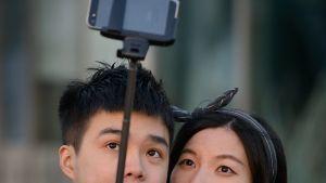 Pariskunta ottaa itsestään selfien selfie-kepin avulla.