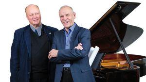 Pianisti Jouni Kuronen ja oopperalaulaja Jorma Hynninen poseeraavat flyygelin edessä.