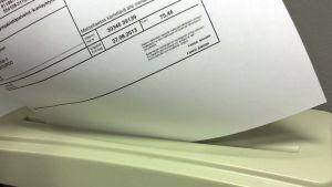 Laskua hävitetään paperisilppurissa.