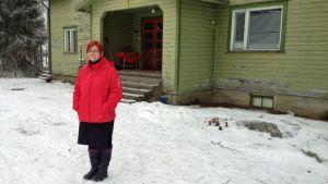 Nainen seisoo lumisella pihalla vanhan vihreän talon edessä.