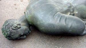 Lähikuva maassa makaavasta pronssipatsaasta