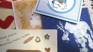 Pöydällä itse tehtyjä joulukortteja