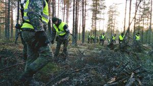Varusmiehet etsivät kadonnutta asetta metsässä.