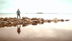 Antti Matikainen seisoo järven rannassa kivien päällä.