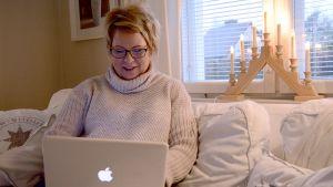 Nainen näppäilee läppäriä sohvalla.