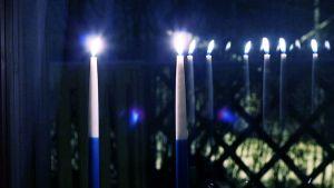 Kaksi sinivalkoista kynttilää ikkunalla.