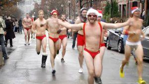 Uimahousuihin pukeutuneet miehet juoksevat kadulla.