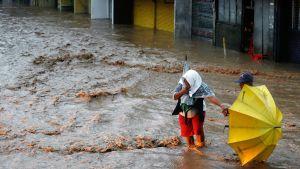 Filippiiniläiset kahlaavat kadulle tulvineessa vedessä Boronganissa.