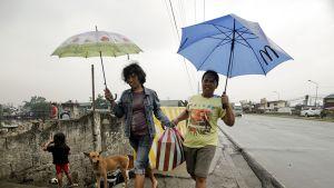 kaksi naista sateenvarjojen kanssa kadulla