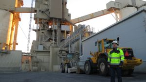 SMA Mineralin Suomen myyntijohtaja Veli-Matti Marttala seisoo kaasulaitoksen edessä. Taustalla myös kalkkitehtaan uunit.