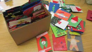 itsetehtyjä joulukortteja pahvilaatikossa ja sen vieressä.