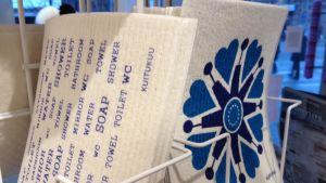 Kauniisti koristeltuja tiskirättejä myyntitelineessä.