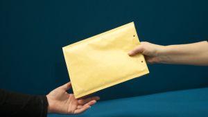 käsi ojentaa kirjekuoren toisen käteen