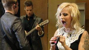 kaksi miespuolista kitaristia ja laulajatar ennen esiintymistä