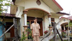 nainen seisoo talonsa edessä