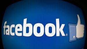 Laajakulmalinssillä otetussa valokuvassa näkyy Facebookin teksti ja peukalologo sinisellä pohjalla.