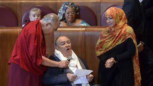 Elokuvaohjaaja Bernardo Bertolucci piti puhettaan Dalai-laman pitäessä mikrofonia ohjaajan rinnan päällä. Oikealla jemeniläinen toimittaja, poliitikko ja ihmisoikeusaktivisti Tawakkul Karman.