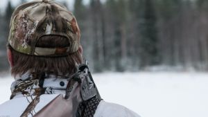 Metsästäjä takaapäin kuvattuna ase olalla.
