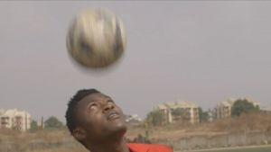 Nuori mies pompottelee jalkapalloa päänsä päällä