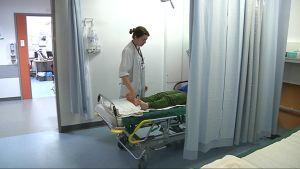 Kuvassa lääkäri, joka tutkii potilaan jalkaa.