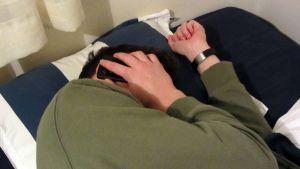 Kuvassa mies makaa sängyllä ja puhuu puhelimeen.