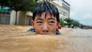 Poika ui Kota Bahrun kadulla tulvavedessä.