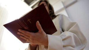 Pappi lukee raamattua.