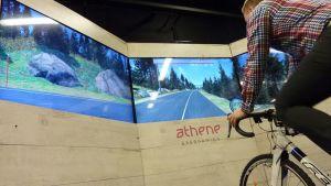 Mies polkee kuntopyörällä näyttöjen edessä