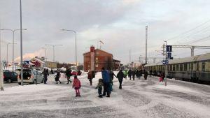 Ihmisiä talvisellä Kemin rautatieasemalla.