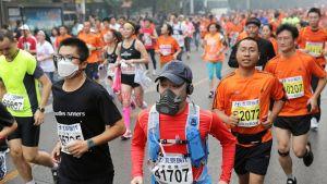 Hengityssuojaimia käyttäviä juoksijoita Pekingin maratonilla.