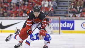 Kanadan Nick Paul hyppää Venäjän Dimitri Judinin niskaan jääkiekkopelissä.