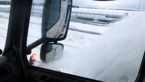 Lumi pöllyää aura-auton ikkunassa
