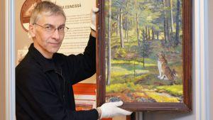 Antti Mäkinen pystyttää näyttelyä Kajaanin Museoon.