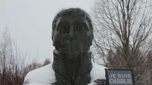 Jaakko Juteinin patsas Hattulassa ja Je suis Charlie -teksti tablettitietokoneen näytöllä