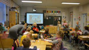 Kajaanin Teppanan koulun ekaloukkalaiset istuvat luokkahuoneessaan ja tekevät vihkoon kirjoitustehtäviä.