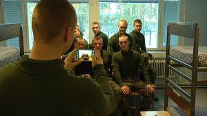 Varusmies ottaa kuvia tovereistaan tuvassa.