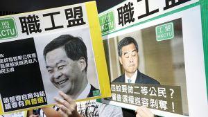 Hongkongilaiset demokratiaa vaativat mielenosoittajat pitelevät Hongkongin aluejohtaja Leung Chun-yingin kuvia hallituksen talon ulkopuolella.