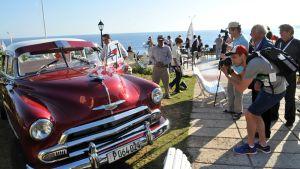 Turistit kuvasivat vanhaa autoa Havannassa toukokuussa 2014.