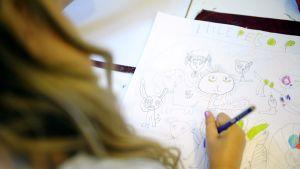 Tyttö piirtää päiväkodissa.