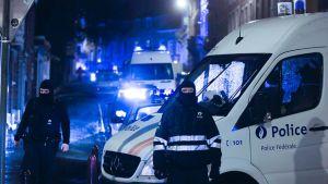 Huputetut poliisit partioivat kadulla.