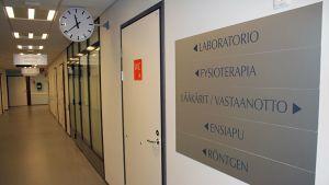 Terveyskeskuksen käytävä ja kyltti seinällä.