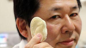 Professori Tsuyoshi Takato esittelee ryhmänsä 3D-tulostimella valmistamaa korvaproteesia.