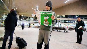 Mies lukee Charlie Hebdo -lehteä Rotterdamin keskusrautatieasemalla.