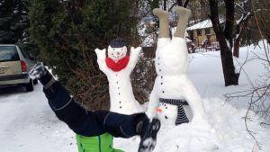 Lapsi seisoo päällään lumiukkojen edessä