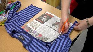 Nainen leikkaa palaa vanhasta t-paidasta