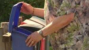 Nainen hakee postin postilaatikosta