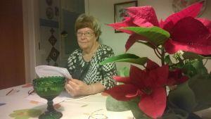 Hämeenlinnan vanhusneuvoston puheenjohtaja Anna-Liisa Torvinen lukee keittiön pöydän ääressä.